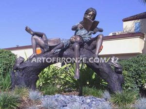 Natures Balance sculpture of girls relaxing on bronze log for playground