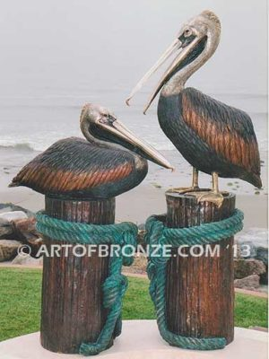Taking a Break bronze statue of playful pelicans on bronze pilings