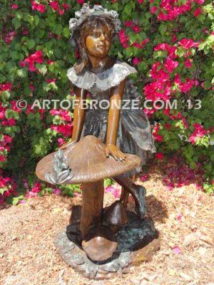 Wonderland bronze sculpture of giant mushroom and standing girl with frog