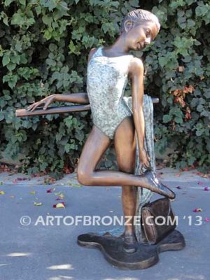 Rehearsal bronze sculpture featuring young ballerina practicing on rail