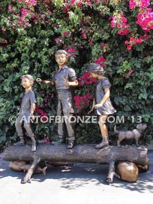 Young Adventurers bronze sculpture of children playing on fallen bronze tree