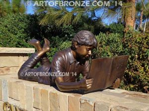 Best in His Class bronze statue of boy lying down reading book