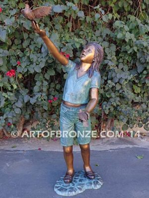 Faith bronze sculpture of young standing girl with doves in her hands