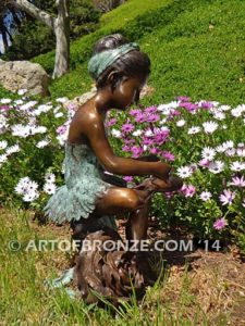 Blooming Youth side view A bronze sculpture of young ballerina sitting tying her slipper