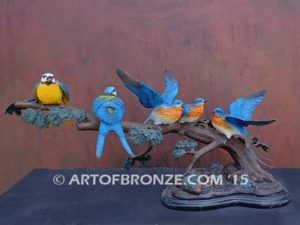 Bronze sculpture of five finches playing together on branch