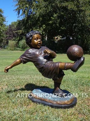 Lil Scorer sculpture of boy playing AYSO soccer bicycle kicking ball into goal