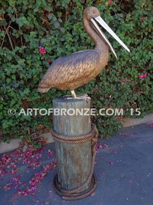 Pelican Perch bronze statue of playful pelican on bronze piling
