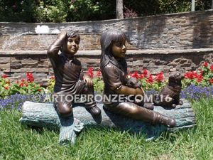 Magic Memories sculpture of log and two children playing atop with their dog