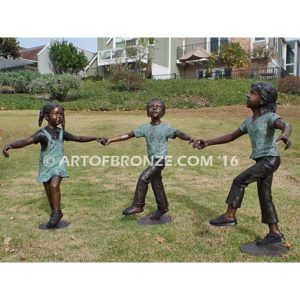 Sing Along bronze sculpture of three kids dancing around and holding hands