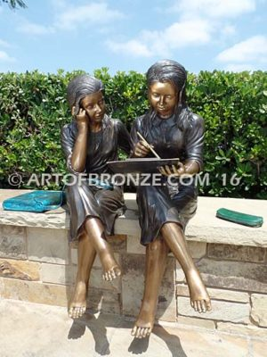 Big Sister Love bronze statue of two girls sitting and drawing