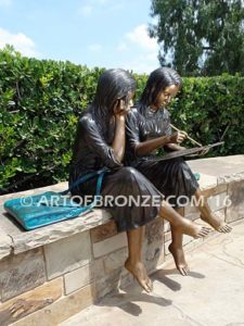 Big Sister Love other side bronze statue of two girls sitting and drawing
