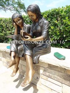 Big Sister Love side view bronze statue of two girls sitting and drawing