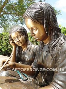 Big Sister Love closeup D bronze statue of two girls sitting and drawing