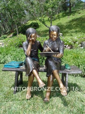 Big Sister bronze statue of two girls sitting on bench drawing