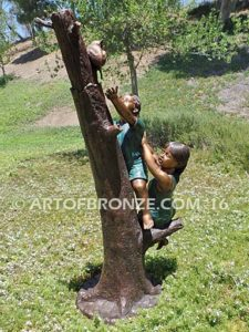 Big Rescue side view A Bronze statue of boy and girl rescuing with cat in tree