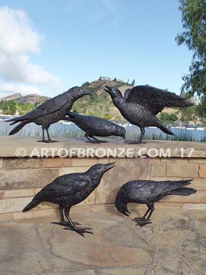 Raven bronze sculpture of ravens playing bench at lake