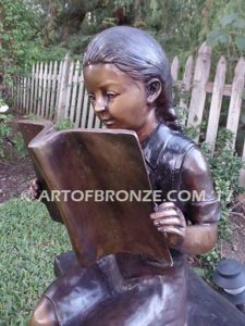 Little learner sculpture of sitting girl reading book on bench
