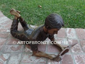 Best in His Class Sm bronze statue of boy lying down reading book
