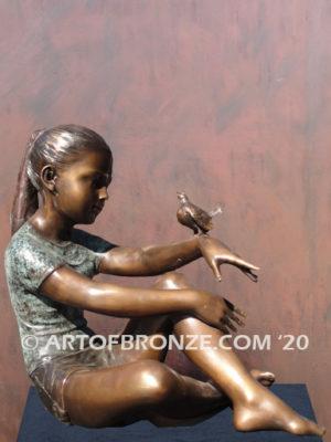 Garden Help bronze sculpture of girl sitting with crossed legs and bird on her hand