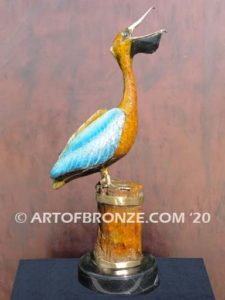 Bronze sculpture of playing pelican swallowing a fish