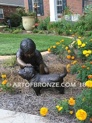 Scrappy bronze garden sculpture of boy playing with his dog